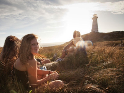 Students relaxing on a hike, with a lighthouse on a horizon