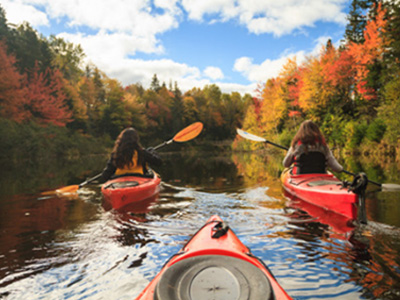 Students kayaking on a river, amidst colourful fall foliage