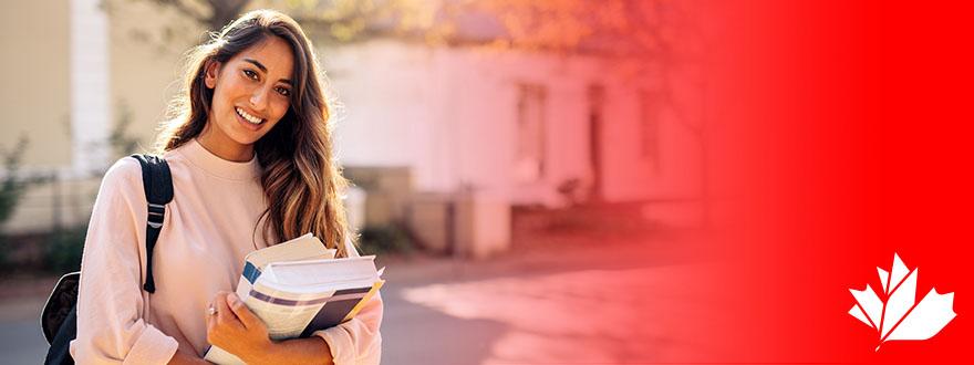 Photo portant la marque ÉduCanada d'une étudiante debout à l'extérieur qui tient des manuels scolaires.